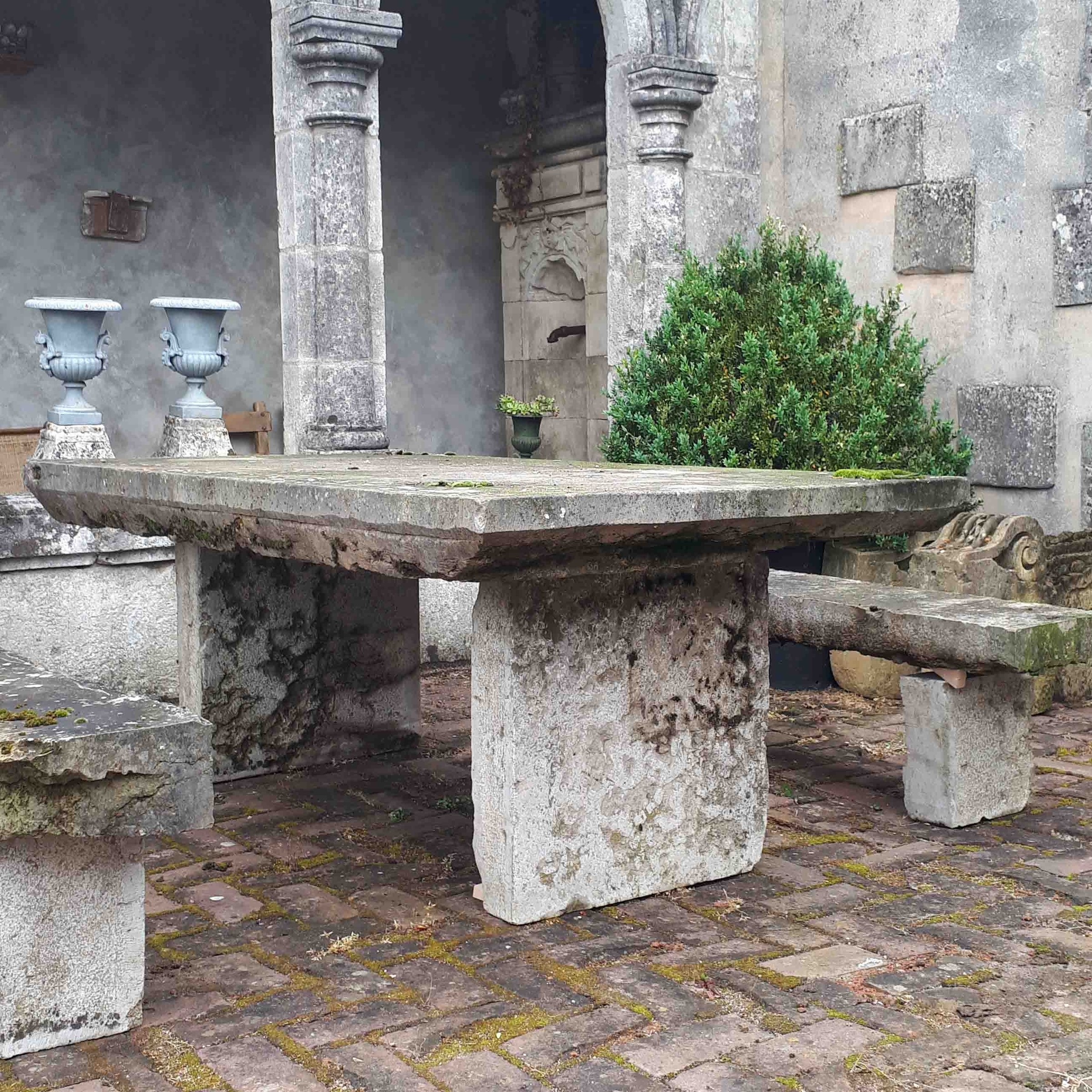Old natural stone garden table with benches