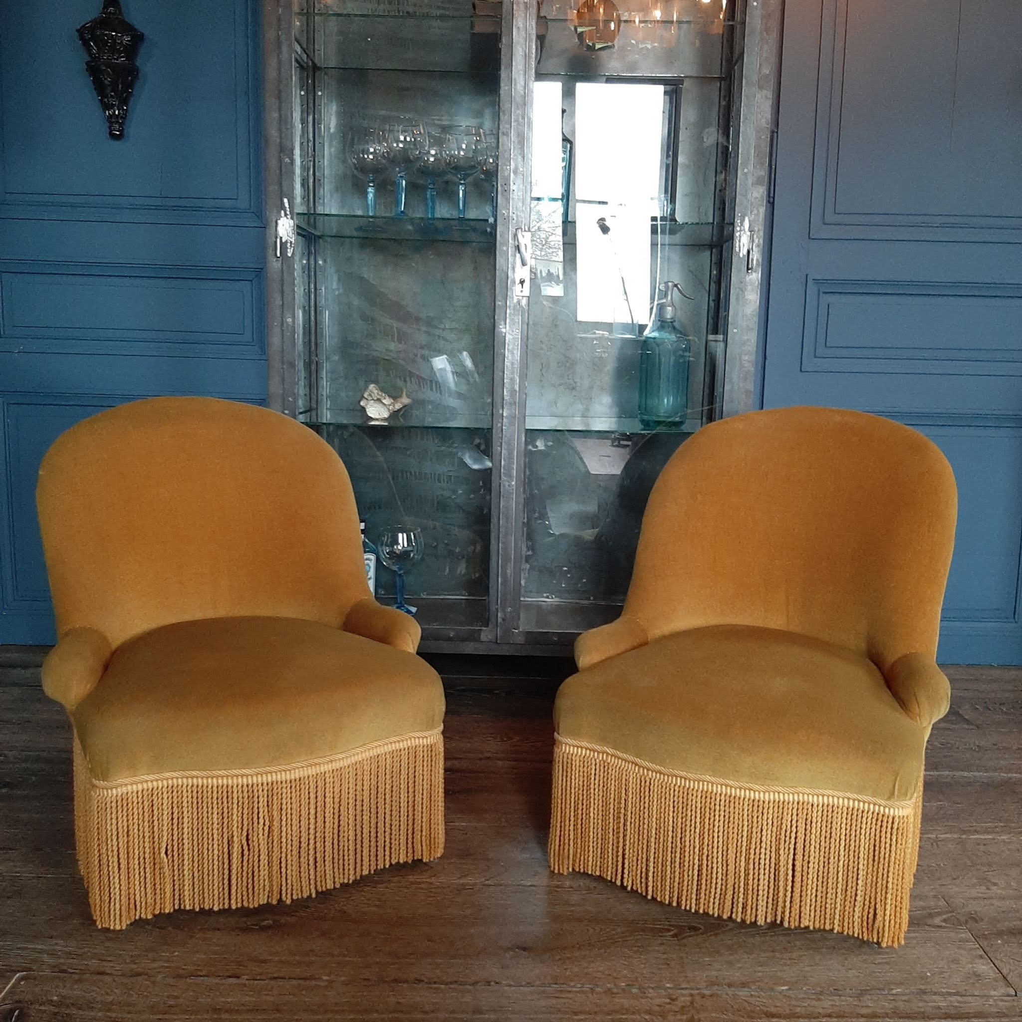 A pair of yellow velvet chairs with fringes
