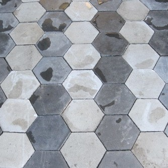 Old cement floor tiles in shades of grey and black