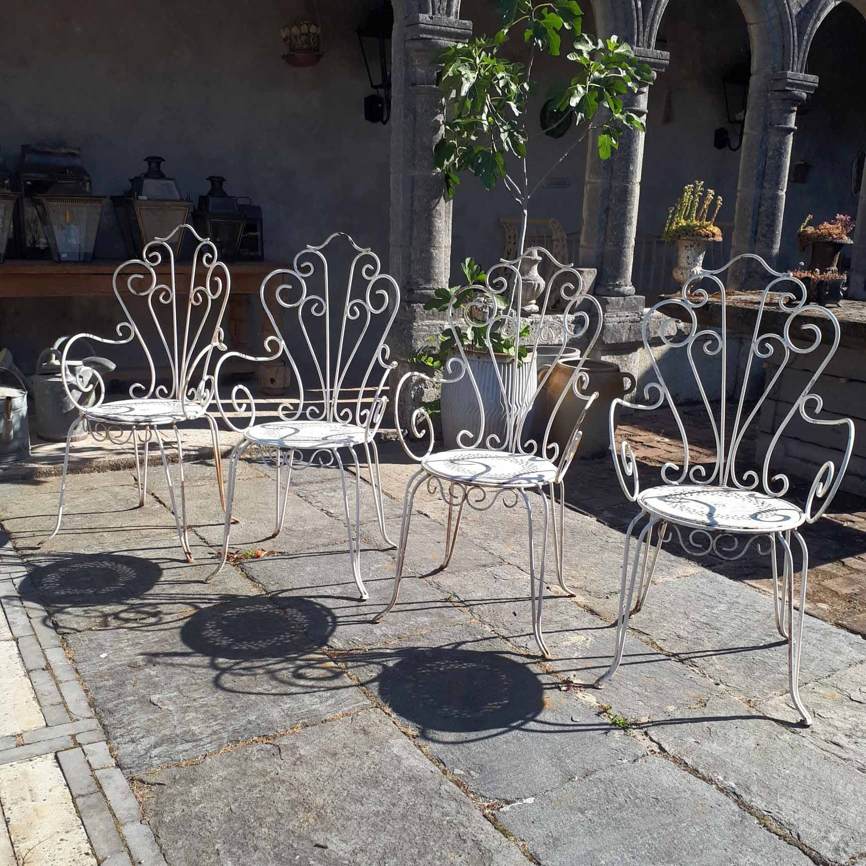 Set of four old iron garden chairs white